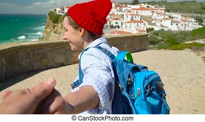 Follow me - happy young woman in a red hat and with a...