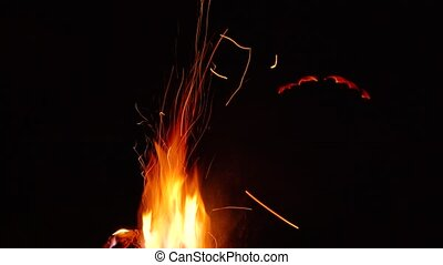 Fire burns at night in a tourist camp. Slow motion -...