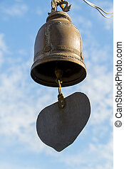 Closeup of metal buddhist bell with heart shape on sky background.