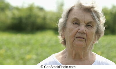 Portrait of serious mature old woman outdoors