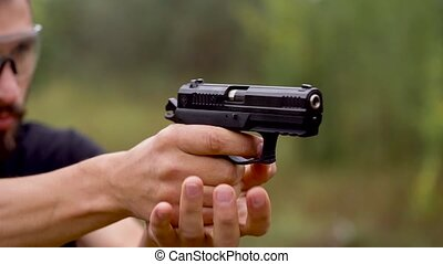 Young man is shooting from a gun, close up - Young man is...
