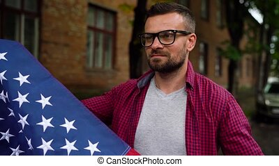 Man waving a US flag while walking along the street - the...