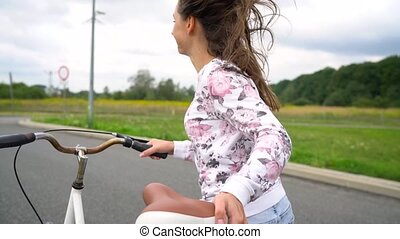 Woman laughing and running down the street with a bicycle....