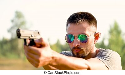 Young man with a gun is aiming to shoot a close up - Young...