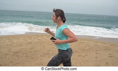 Athletic woman running along the beach. Slow motion -...