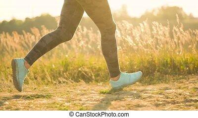 Woman runs outdoors at sunset - Legs of a woman running...