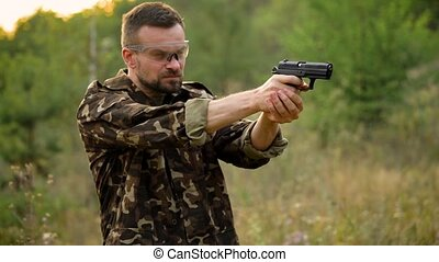 Young man in camouflage shooting from a gun, close up. Slow...