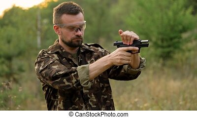 Young man in camouflage shooting from a gun, close up