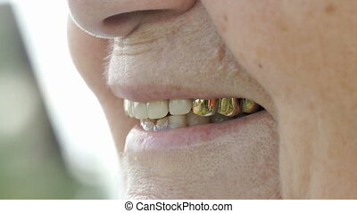 Smiling mouth of mature old woman with false teeth. Close up