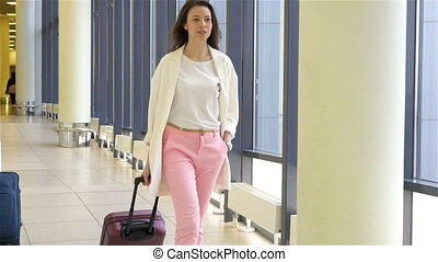 Tourist girl with baggage in international airport walking...