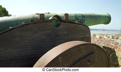 An ancient cast-iron cannon in the foreground and roofs of...