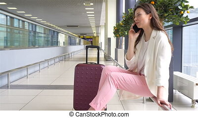 Portrait of young caucasian woman an airport waiting for her...