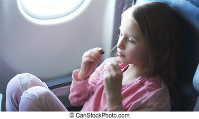 Adorable little girl traveling by an airplane. Cute kid...
