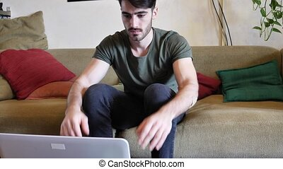 Young man doing videochat at home on laptop PC - Young...
