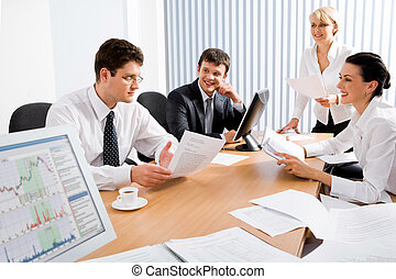 Business meeting - Portrait of four professionals sitting at...