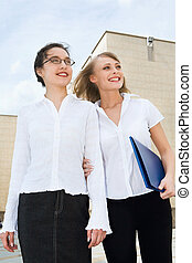 Prospect - Two businesswomen looking upwards holding blue...