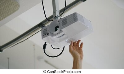Man's hand switch on of projector on ceiling in loft or...