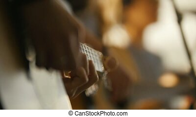 Rock artists playing acoustic guitar at concert, close up