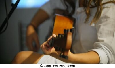 Woman with guitar at stage in loft, close up - Woman with...