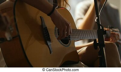 Beautiful girl with guitar at stage in loft, close up view