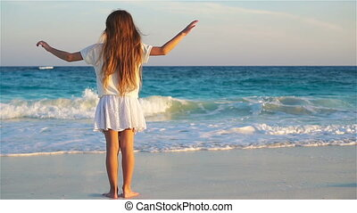 Adorable happy little girl on white beach looking on the...