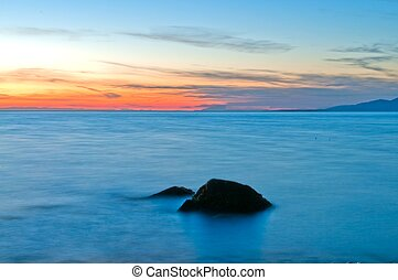 Sunset on beach with rock
