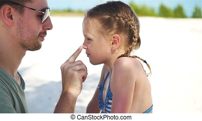Parent applying sun cream to kid nose. Portrait of cute girl...