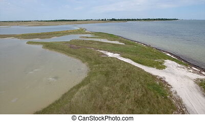 Aerial shot of the Black Sea shoal with green wetland and...