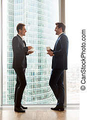 Male coworkers enjoying cup of coffee during break - Two...