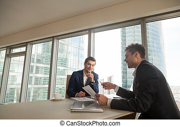 Two businessmen discussing growth rates on meeting -...