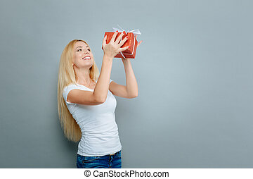 Charming woman holding red box with present - I am happy....