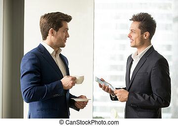 Two successful businessmen discussing business - Handsome...