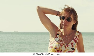 Young woman wearing sunglasses standing at the sea front
