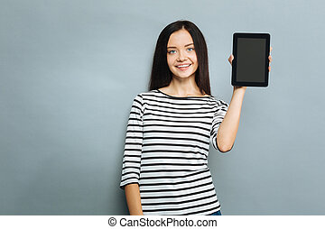Positive delighted young woman demonstrating her device - It...