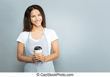 Charming young female holding cup with favorite drink -...