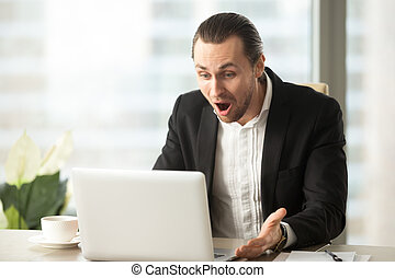 Frustrated young businessman looks at laptop screen...