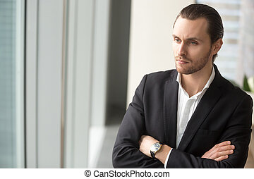 Serious young businessman in deep though about corporate...