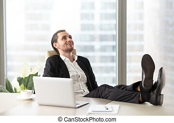 Happy smiling businessman relaxing at workplace in modern...