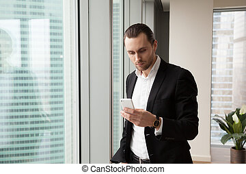 Serious young handsome businessman in modern office looking...