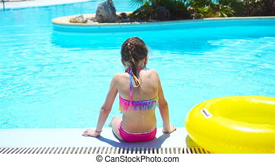 Little girl with inflatable rubber circle in swimming pool -...