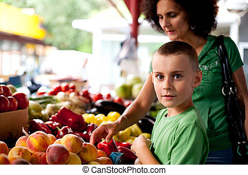 Shopping at farmers market - Mother and child shopping at...