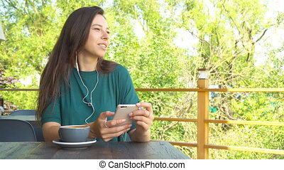 Woman using app on smartphone in cafe drinking coffee...