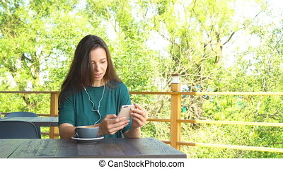 Woman with smartphone in cafe drinking coffee smiling and...