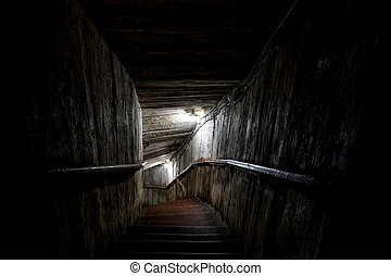 Stairs going into a dark tunnel