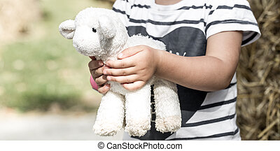 little girl holding a toy sheep ,the concept of childhood...