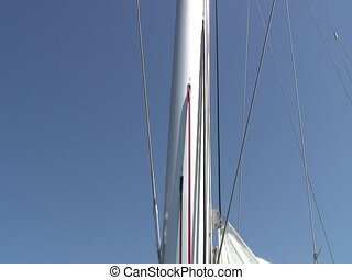 Crew member on top of the mast of a catamaran