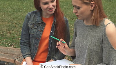 Two girls studying outdoors - Students sitting on a bench...