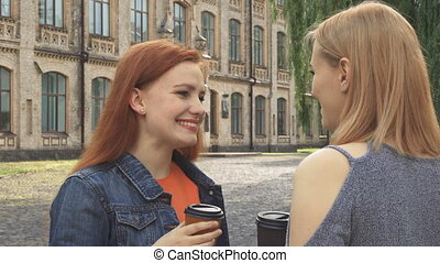 Two girls having a talk and drinking coffee - Blonde talking...