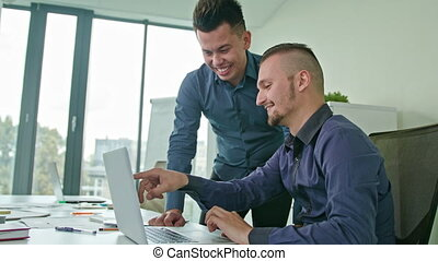 Two Man Discussing Ideas Using Laptop