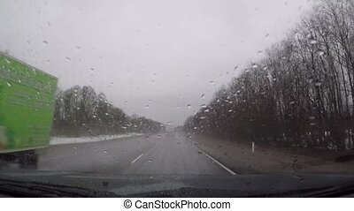 Driving in a car in bad rainy autumn weather